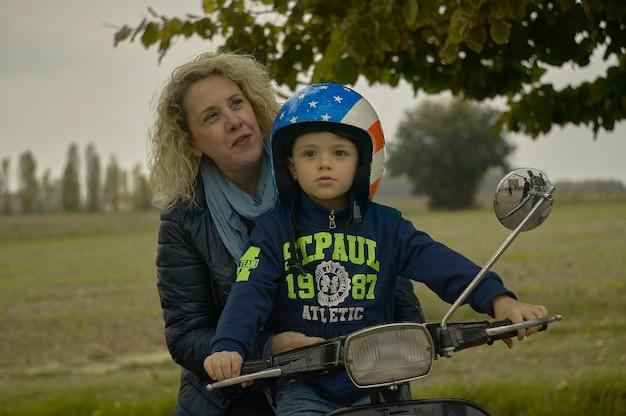 Rovigo, italie 19 février 2020 : mère et fils souriants voyagent sur le scooter