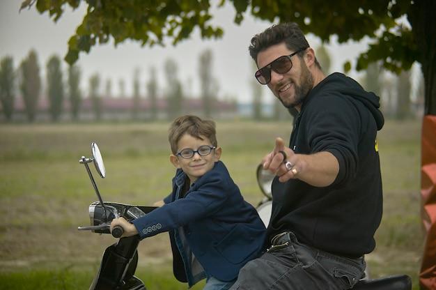 Rovigo, italie 19 février 2020 : père et fils souriants voyagent sur le scooter