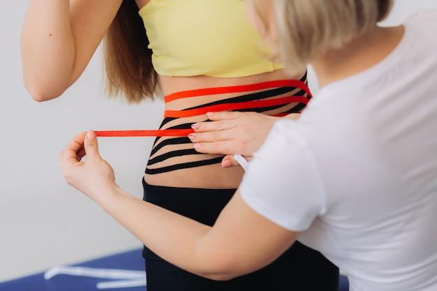 Ruban adhésif kinesio sur le ventre de la femme. jeune femme caucasienne avec du ruban élastique thérapeutique kinésiologie sur son ventre.