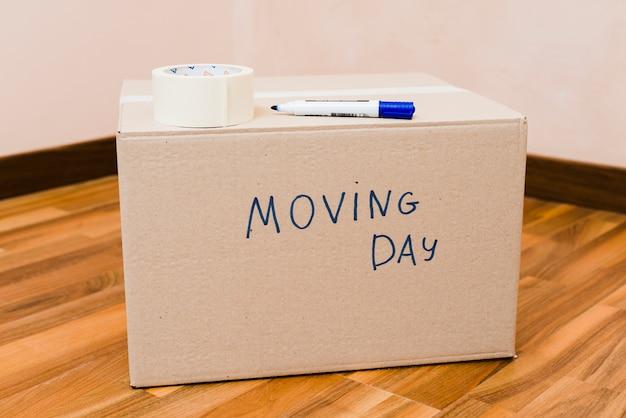 Ruban adhésif et marqueur sur la boîte en carton du jour du déménagement, sur le plancher de bois franc