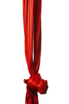 Ruban aérien rouge noué pour les acrobaties aériennes et la gymnastique accroché au mur blanc. concept d'occupation pour enfants et adultes avec le développement de la flexibilité et de l'appareil vestibulaire