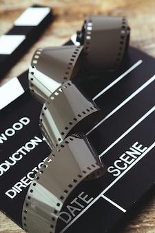 Ruban d'appareil photo bobine vintage et clap sur bois