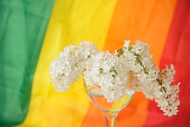 Ruban arc-en-ciel lgbt et bouquet de lilas blanc en verre. symbole de ruban de fierté. espace de copie. concept de droits lgbt.