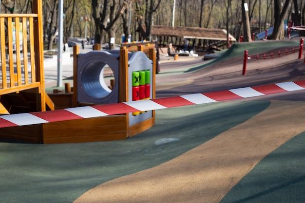 Ruban d'avertissement rouge sur l'aire de jeux pour enfants fermée, en raison de la quarantaine covid-19, aire de jeux de quarantaine fermée.