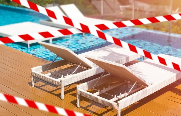 Ruban barrière quarantaine isolement interdiction d'entrée ne pas traverser chaise longue vide au bord de la piscine propre