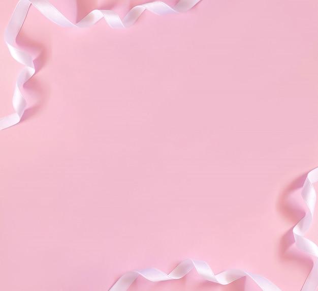 Ruban blanc bouclé festif sur surface rose