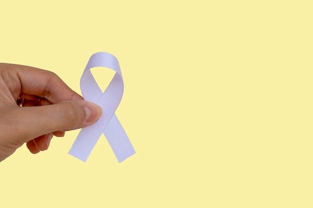 Le ruban blanc sur la main d'une femme représente le programme de prévention de la santé mentale. janvier blanc.