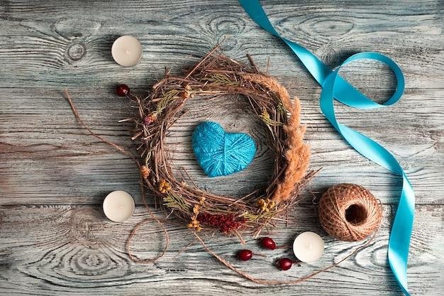 Ruban bleu, coeur, bougies et une couronne sur un fond en bois naturel.