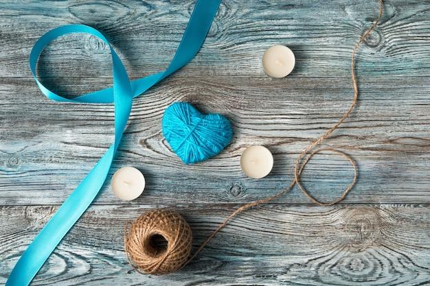 Ruban bleu et coeur avec des bougies sur un fond en bois.