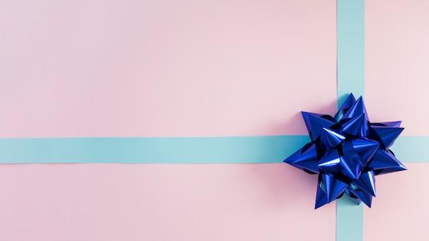 Ruban bleu décoratif et archet sur fond rose