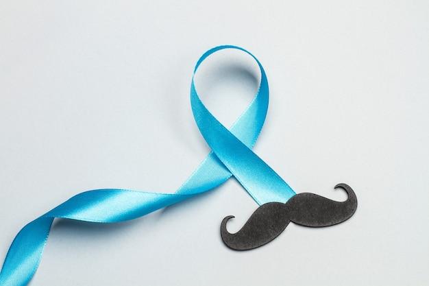Un ruban bleu et une moustache noire sur fond noir gris