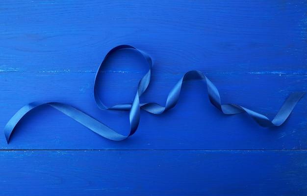 Ruban bleu en soie torsadée sur un fond en bois bleu