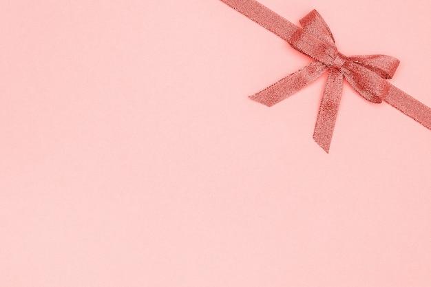 Ruban brillant décoratif avec noeud sur fond rose pastel avec espace copie pour le texte