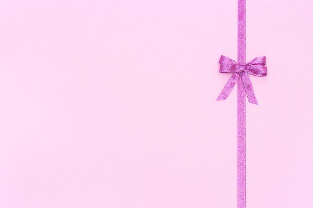 Ruban brillant décoratif avec noeud sur fond rose pastel