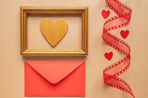 Ruban décoratif torsadé et enveloppe rouge avec des coeurs rouges.