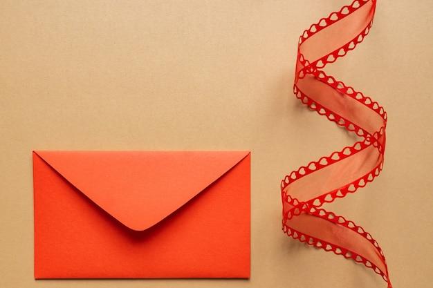 Ruban décoratif torsadé et enveloppe rouge.