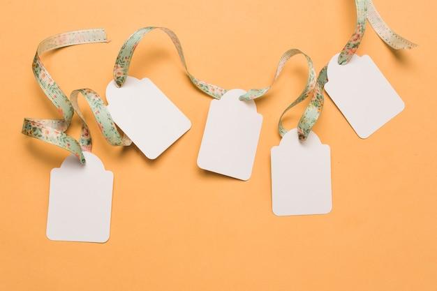 Ruban de designer à travers des étiquettes vides disposées sur une surface jaune vif