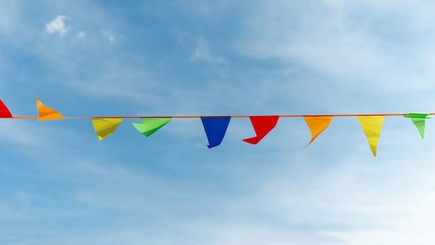 Ruban festif composé de triangles multicolores sur fond de ciel.