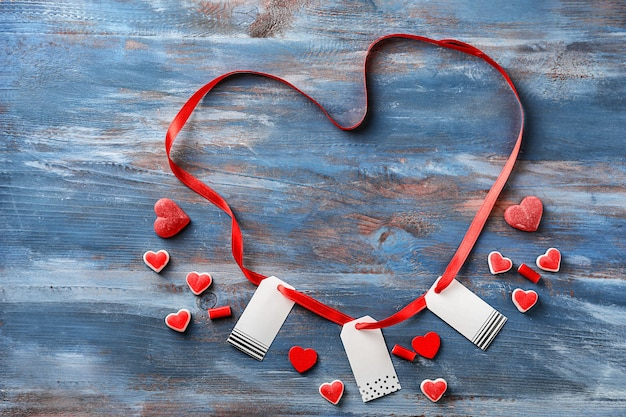 Ruban en forme de coeur avec des étiquettes et des bonbons à la gelée sur fond de bois de couleur
