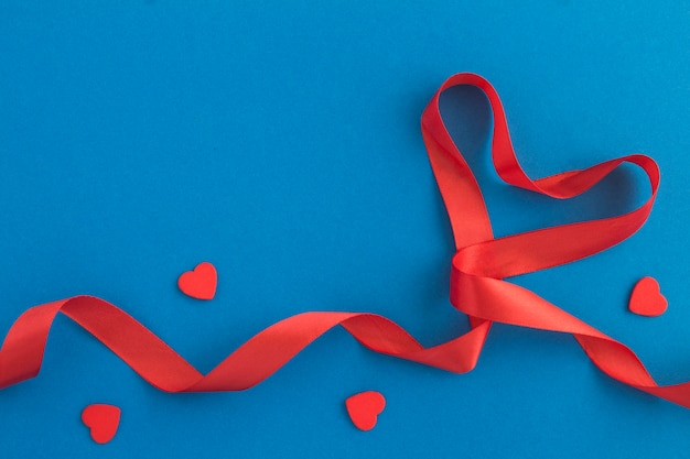 Ruban en forme de coeur rouge et petits coeurs sur la surface bleue