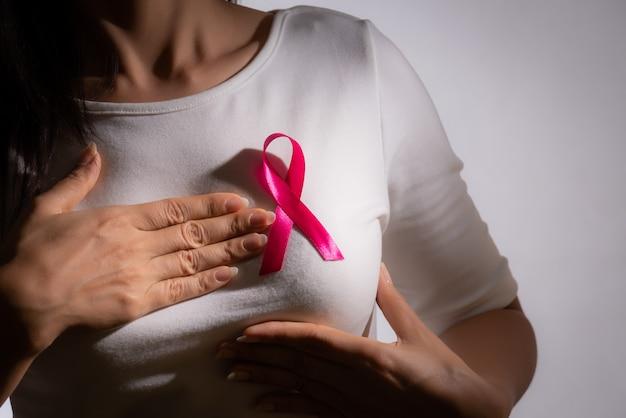 Ruban d'insigne rose sur la poitrine de la femme pour soutenir la cause du cancer du sein. concept de soins de santé.