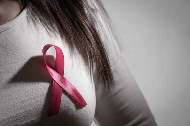 Ruban d'insigne rose sur la poitrine de la femme pour soutenir la cause du cancer du sein
