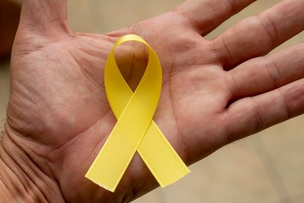 Ruban jaune sur la paume. jaune de septembre. campagne de prévention du suicide