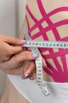 Ruban kinesio sur l'abdomen pour raffermir la peau après l'accouchement ou la perte de poids. le spécialiste mesure la taille des patients.