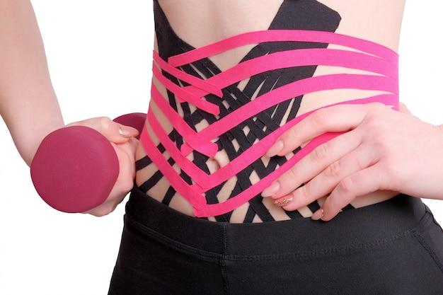 Ruban kinesio croisé sur l'abdomen d'une fille avec un haltère à la main.