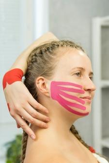 Ruban kinesio sur le visage d'une jeune femme pour raffermir la peau. procédure de beauté de lifting. physiothérapie et kinésiologie.