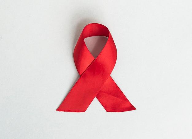 Ruban médical rouge pour le sida et la sensibilisation à la journée du vih noeud de satin enroulé sur fond bleu