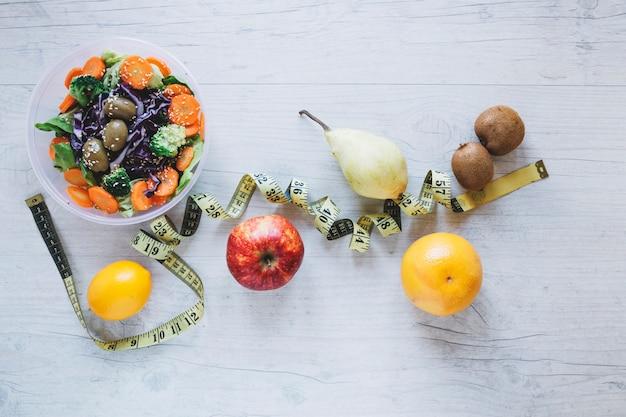 Ruban à mesurer au milieu des fruits et de la salade