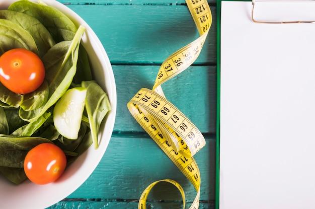 Ruban à mesurer et bol d'ingrédients végétaux sur un plateau en bois