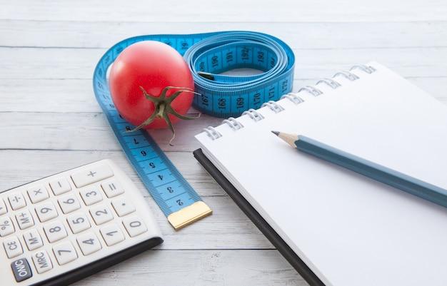 Ruban à mesurer et calculatrice avec tomate juteuse, concept de saine alimentation et minceur
