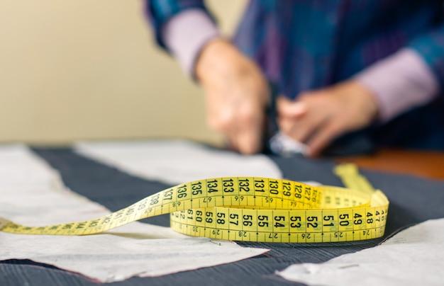 Ruban à mesurer avec couturière coupant le tissu avec des ciseaux en arrière-plan. mise au point sélective sur le ruban à mesurer au premier plan