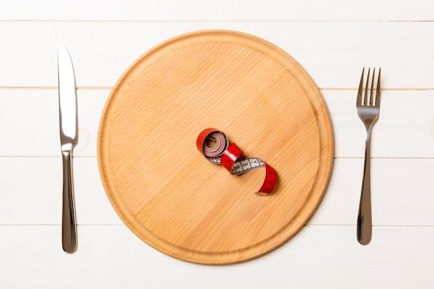 Ruban à mesurer dans une assiette avec une fourchette et un couteau des deux côtés sur du bois. vue de dessus de la perte de poids
