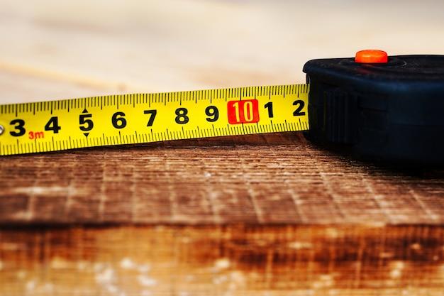 Ruban à mesurer déplié sur une planche en bois