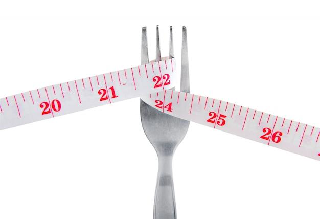 Ruban à mesurer emballage fourche perdre poids concept isolé sur blanc