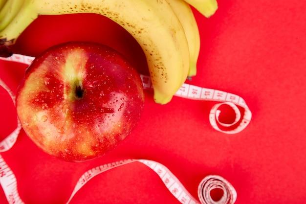 Ruban à mesurer enroulé autour d'une pomme rouge et d'une banane