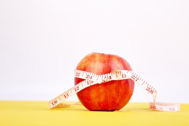 Ruban à mesurer enroulé autour d'une pomme rouge