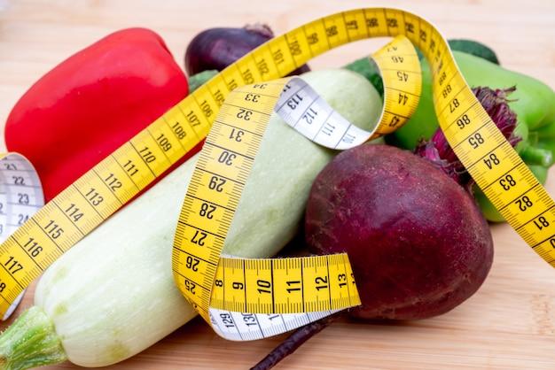 Ruban à mesurer jaune et légumes sur une planche à découper en bois. régime de mode de vie sain.
