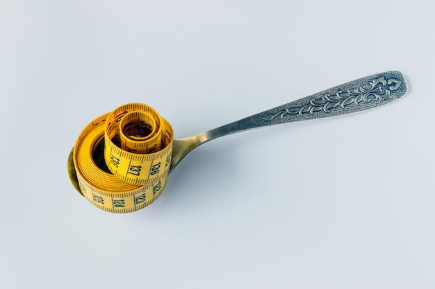 Le ruban à mesurer jaune roulé se trouve sur la cuillère