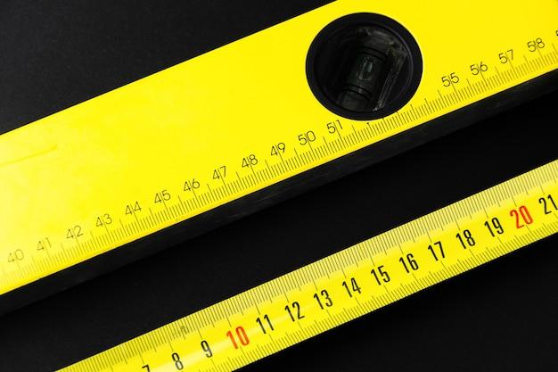 Ruban à mesurer et niveau de construction en jaune sur fond noir