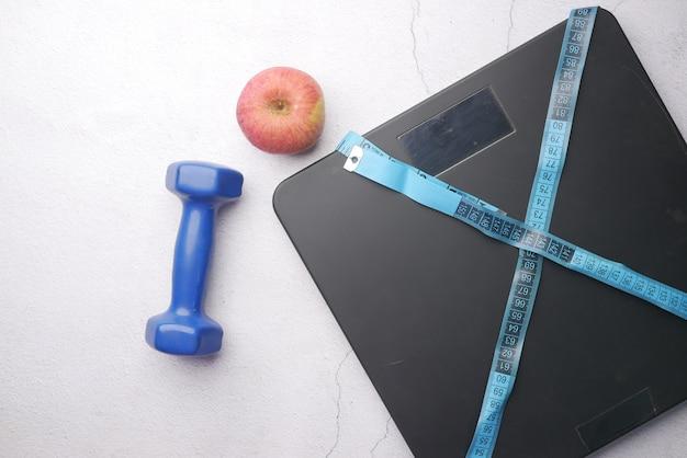Un ruban à mesurer et un pèse-personne sur plancher en bois
