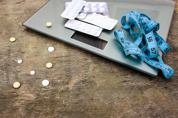 Ruban à mesurer, des pilules et des échelles sur fond en bois.