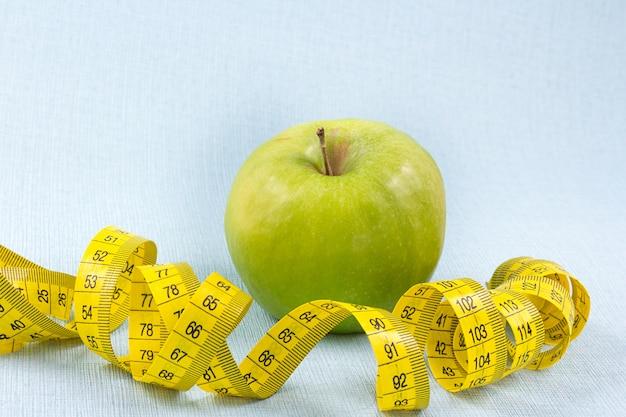 Ruban à mesurer avec pomme verte sur fond bleu. concept de perte de poids.
