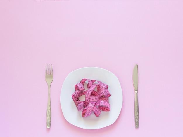 Ruban à mesurer rose couché sur une assiette en forme de spaghetti, couteau et fourchette sur fond rose