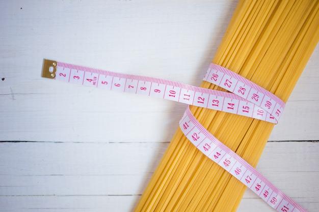 Ruban à mesurer, thème de l'alimentation. avec des tas de spaghettis de pâtes italiennes non cuites