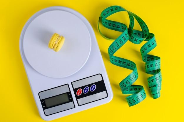 Ruban à mesurer vert, balance de cuisine numérique avec macarons sur jaune