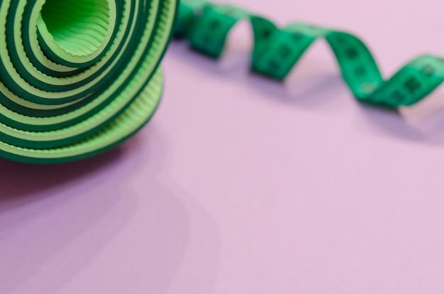 Un ruban à mesurer vert tordu en spirale et un tapis de fitness reposent sur un fond violet